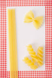 Pasta framed background. Pasta on white background and red checkered frame Royalty Free Stock Images