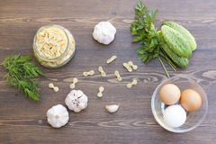 Pasta and fresh eggs with fresh vegetables and herbs. Pasta and fresh eggs in a glass with fresh vegetables and herbs royalty free stock image