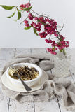 Pasta with fresh pioppini mushrooms on plate on white table with branch of pink berries on vase Royalty Free Stock Image