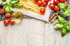 Pasta with fresh tomatoes, basil and olive oil on light shabby rustic background, top view, border. Stock Images