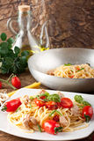 Pasta with fresh tomatoes, tuna and basil. On complex background Stock Photo