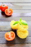Pasta and fresh tomatoes on wooden surface Stock Photos