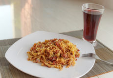 Pasta with fried meat on white plate and glass of juice Stock Photography