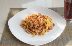 Pasta with fried meat on white plate and glass of juice Stock Image