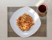 Pasta with fried meat on white plate and glass of juice Royalty Free Stock Image