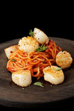 Pasta with fried scallops, oragano and tomato sauce on black woo Royalty Free Stock Photo