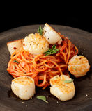Pasta with fried scallops, oragano and tomato sauce Stock Photos