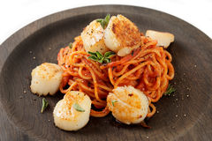Pasta with fried scallops and tomato sauce on black plate Stock Photography