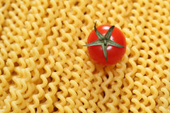 Pasta fusilli and cherry tomato. Pasta Fusilli (Fusilli lunghi bucati) and cherry tomato. Close-up Stock Image