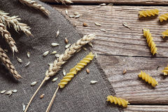 Pasta fusilli and a grain ears on rustic wood. Metamorphosis whe Royalty Free Stock Photo