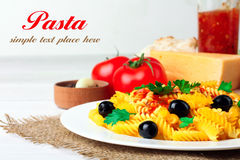 Pasta. Fusilli pasta and olives in the dish by the fresh tomatoes and peppers with garlic and cheese lying on a wooden white background with space for your Royalty Free Stock Images