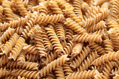 Pasta (Fusilli). Raw brown pasta (Fusilli) background. Close-up Royalty Free Stock Images