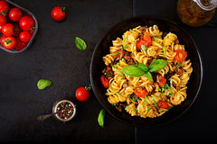 Pasta Fusilli with tomatoes, beef and basil in black bow Stock Photos