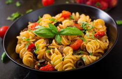 Pasta Fusilli with tomatoes, beef and basil in black bowl Royalty Free Stock Photography