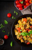 Pasta Fusilli with tomatoes, beef and basil in black bowl Stock Photos