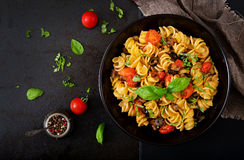 Pasta Fusilli with tomatoes, beef and basil in black bowl Royalty Free Stock Images