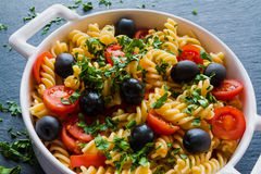 Pasta (fusilli) in white pan on black slate background Stock Image