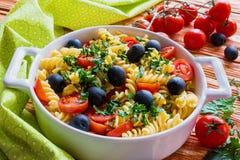 Pasta (fusilli) in white pan on wooden background Stock Photos