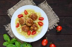 Pasta futsilli with meat balls, cherry tomatoes, basil on a white plate on a dark wooden background. Royalty Free Stock Photos