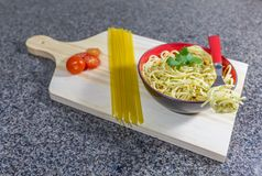 Pasta in garlic and oil, served in a bowl with bacon and tomatoes royalty free stock photography