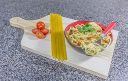Noodle in garlic and oil, served in a bowl with bacon and tomatoes royalty free stock photo