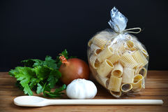 Pasta, garlic and onion with a wooden spoon, ingre Stock Images
