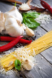 Pasta, garlic, pepper, basil and parmigiano. Traditional ingredients of italic cuisine - pasta, garlic, peppers, basil and grained parmigiano. Selective focus Royalty Free Stock Images