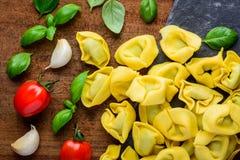 Pasta gialla dei tortellini con la cottura degli ingredienti Immagini Stock
