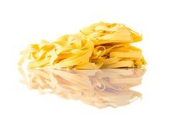 Pasta gialla di Taglionlini di tagliatelle su fondo bianco Fotografia Stock Libera da Diritti