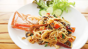 Pasta with giant prawn, olives, tomatoes, and chilli on wood background royalty free stock image