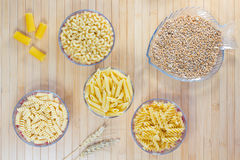 Pasta in glass plates. Wheat grains. Wheat spikelets. Flat lay stock image