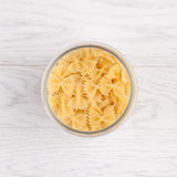 Pasta in glass pot. On white wooden background Royalty Free Stock Photography