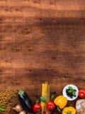 Pasta, grönsaker, örter och kryddor för italiensk mat på den lantliga trätabellen, bästa sikt, kopieringsspac arkivbilder
