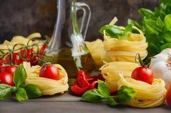 Pasta, grönsaker, örter och kryddor för italiensk mat på träbakgrunden Royaltyfri Bild