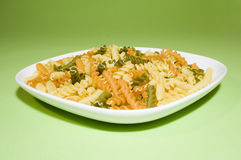 Pasta on green background. (on white plate royalty free stock photography