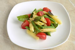 Pasta with green beans, cherry tomatoes and basil Stock Images