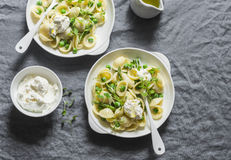 Pasta with green peas, asparagus and fresh ricotta. On a gray background, top view. Royalty Free Stock Photography