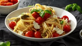 Pasta with green pesto sauce, roasted cherry tomatoes and mozzarella cheese in white plate on dark rustic background royalty free stock photography
