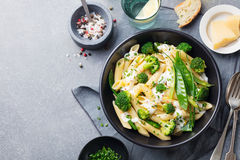 Pasta with green vegetables and creamy sauce in black bowl. Top view. Copy space. Royalty Free Stock Image