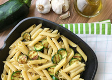 Pasta with grilled zucchini, garlic and olive oil in a frying pan. Ingredients on background. Top view. Royalty Free Stock Photo