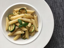 Pasta and grilled zucchini served on white plate. Top view. Stock Photo