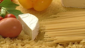 Pasta, ham, cheese, egg and vegetables with rustic sackcloth on yellow background stock video