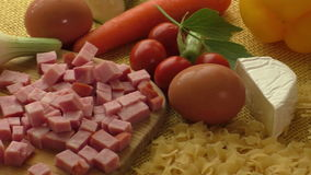 Pasta, ham, cheese, egg and vegetables with rustic sackcloth. On yellow backgrounde stock video footage