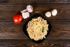 Pasta with ham and chicken on a black plate on a dark wooden background (spirals pasta). Pasta with ham and chicken on a black plate on a dark wooden background royalty free stock photo