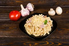 Pasta with ham and chicken on a black plate on a dark wooden background (spirals pasta). Pasta with ham and chicken on a black plate on a dark wooden background stock images