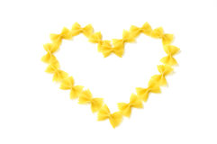 Pasta in a heart shape on white. Closeup of italian pasta  a heart shape, farfalle  on white  background Royalty Free Stock Images