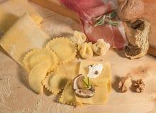 Pasta hecha a mano cruda y raviolis hechos en casa italianos, abierto y cerrado, llenados de queso del ricotta y de setas Foto de archivo