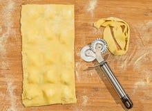 Pasta hecha a mano de los raviolis, cubierta con la harina y el cortador de la pasta de la rueda colocados en la tabla de madera Foto de archivo