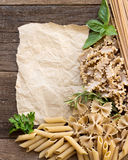 Pasta, herbs and paper on wooden background Stock Photo