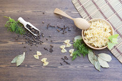 Pasta with herbs and spices on wooden table. Pasta with herbs and spices on dark wooden table stock photography